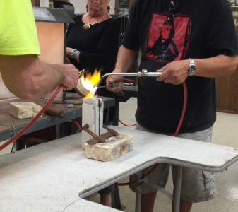 Pouring melted silver into bracelet mold.